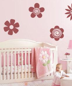 Primer izgleda temno rdeče samolepilne stenske nalepke Cveti A na roza steni nad zibelko v otroški sobi.