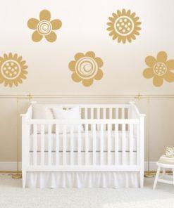 Primer izgleda zlate samolepilne stenske nalepke Cveti B na beli steni nad zibelko v otroški sobi.