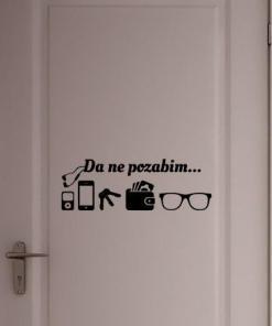 Primer izgleda črne samolepilne stenske nalepke Da ne pozabim na belih vratih.Nalepka vsebuje napis: Da ne pozabim...