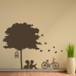 Primer izgleda rjave samolepilne stenske nalepke Deček in deklica pod drevesom 2 na beli steni na hodniku.