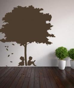 Primer izgleda rjave samolepilne stenske nalepke Deček in deklica pod drevesom na beli steni v knjižnjici.