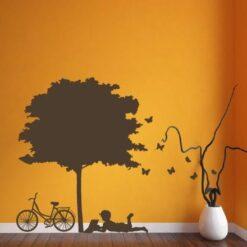 Primer izgleda rjave samolepilne stenske nalepke Deček s knjigo pod drevesom na oranžni steni v sobi.