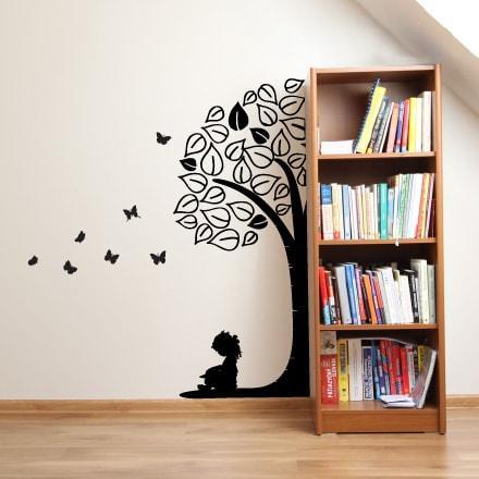 Primer izgleda črne samolepilne stenske nalepke Deklica pod drevesom z metulji na beli steni ob omari s knjigami.