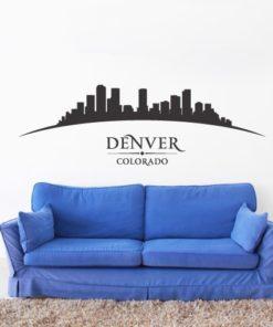 Primer izgleda črne samolepilne stenske nalepke Denver ukrivljen na beli steni nad sedežno v dnevni sobi.
