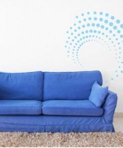 Primer izgleda svetlo modre samolepilne stenske nalepke Dotty na beli steni nad zofo.