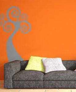 Primer izgleda sive samolepilne stenske nalepke Drevo Art na oranžni steni nad zofo.