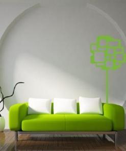 Primer izgleda zelene samolepilne stenske nalepke Drevo s kvadrati na beli steni nad zeleno sedežno.