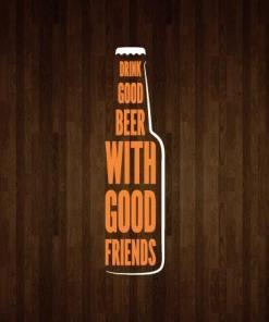 Primer izgleda dvobarvne samolepilne stenske nalepke Drink good beer with good friends na leseni steni v dnevni sobi. Nalepka ima napis, ki se glasi: Drink good beer with good friends.