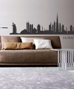Primer izgleda grafitno sive samolepilne stenske nalepke Dubai 1 na bež steni v dnevni sobi.
