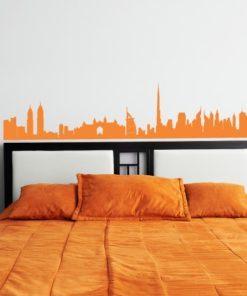 Primer izgleda oranžne samolepilne stenske nalepke Dubai orange na beli steni v spalnici.