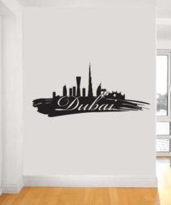Primer izgleda črne samolepilne stenske nalepke Dubai packa na beli steni.