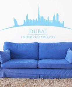 Primer izgleda modre samolepilne stenske nalepke Dubai ukrivljen na beli steni v dnevni sobi.