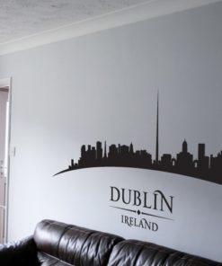 Primer izgleda črne samolepilne stenske nalepke Dublin ukrivljen na beli steni v dnevni sobi.