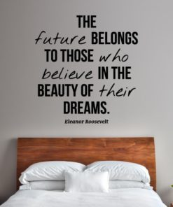 Primer izgleda črne samolepilne stenske nalepke Eleanor Roosevelt Citat - The future belongs na beli steni v spalnici. Nalepka je citat Eleanor Roosevelt, ki se glasi: The future belongs to those who believe in the beauty of their dreams.