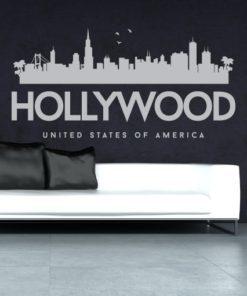 Primer izgleda sive samolepilne stenske nalepke Hollywood na sivi steni nad zofo v dnevni sobi.