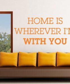 Primer izgleda oranžne samolepilne stenske nalepke Home is wherever Im with you na bež steni v dnevni sobi.