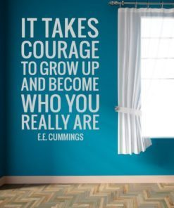 Primer izgleda bele samolepilne stenske nalepke E. E. Cummings Citat - It takes courage na modri steni v dnevni sobi. Nalepka je citat E.E. Cummings, ki se glasi: It takes courage to grow up and become who you really are.