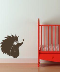 Primer izgleda čokoladno rjave samolepilne stenske nalepke Ježek na beli steni v otroški sobi.