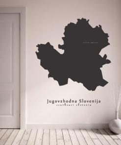 Primer izgleda črne samolepilne stenske nalepke Jugovzhodna Slovenija na bež steni v dnevni sobi.