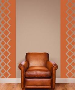 Primer izgleda črne samolepilne stenske nalepke Kara vzorci zrcalno na beli steni ob fotelju.
