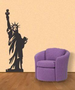 Primer izgleda črne samolepilne stenske nalepke Kip svobode 2 na oranžni steni v dnevni sobi.