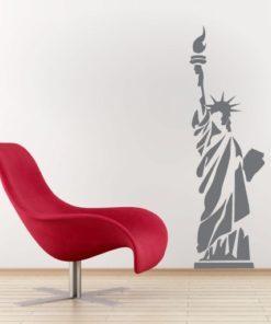 Primer izgleda grafitno sive samolepilne stenske nalepke Kip svobode na beli steni v dnevni sobi.