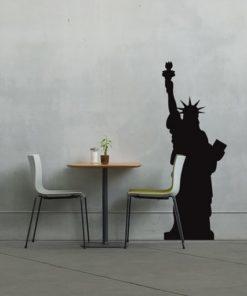 Primer izgleda črne samolepilne stenske nalepke Kip svobode 2x na sivi steni v jedilnici.