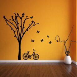 Primer izgleda črne samolepilne stenske nalepke Kolo pod drevesom v jeseni na oranžni steni v dnevni sobi.