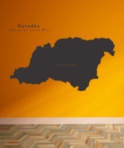 Primer izgleda črne samolepilne stenske nalepke Koroška na oranžni steni v dnevni sobi.