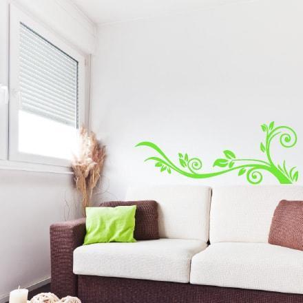 Primer izgleda zelene samolepilne stenske nalepke Kotni ornament na beli steni v dnevni sobi.
