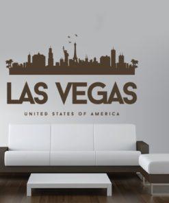 Primer izgleda čokoladno rjave samolepilne stenske nalepke Las Vegas Luna na beli steni nad zofo v dnevni sobi. Na nalepki piše: Las Vegas, United Sates of America