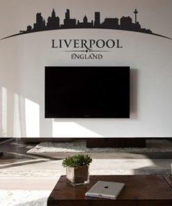 Primer izgleda črne samolepilne stenske nalepke Liverpool ukrivljen na beli steni v dnevni sobi.