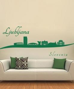 Primer izgleda zelene samolepilne stenske nalepke Ljubljana zavito na bež steni v dnevni sobi.