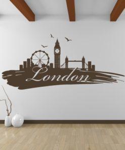 Primer izgleda čokoladno rjave samolepilne stenske nalepke London packa na beli steni v dnevni sobi.