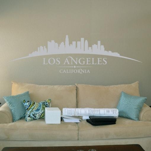 Primer izgleda sive samolepilne stenske nalepke Los Angeles ukrivljen na bež steni nad sedežno v dnevni sobi. Na nalepki piše: Los Angeles, California