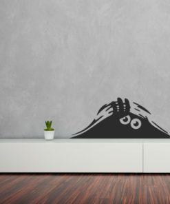 Primer izgleda črne samolepilne stenske nalepke Mala pošast na beli steni v otroški sobi.