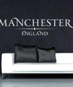 Primer izgleda bele samolepilne stenske nalepke Manchester England napis na črni steni v dnevni sobi.