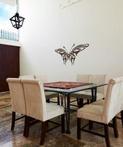 Primer izgleda čokoladno rjave samolepilne stenske nalepke Metulj 1 na beli steni v jedilnici.