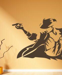Primer izgleda čokoladno rjave samolepilne stenske nalepke Michael Jackson 2 na oranžni steni v dnevni sobi.