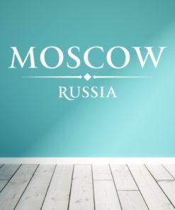 Primer izgleda bele samolepilne stenske nalepke Moscow Russia napis na turkizno zeleni steni v dnevni sobi.