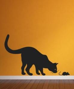 Primer izgleda črne samolepilne stenske nalepke Muca in miš na oranžni steni v dnevni sobi.