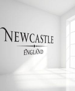 Primer izgleda črne samolepilne stenske nalepke New Castle England napis na beli steni v dnevni sobi.