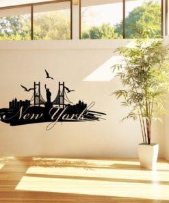 Primer izgleda črne samolepilne stenske nalepke New York packa na beli steni v dnevni sobi. Na nalepki piše: New York