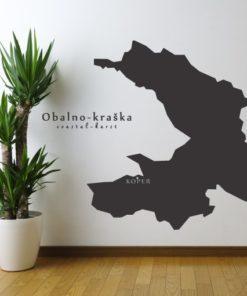 Primer izgleda črne samolepilne stenske nalepke Obalno - kraška na beli steni v dnevni sobi.
