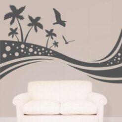 Primer izgleda grafitno sive samolepilne stenske nalepke Palme z galeboma na bež steni v dnevni sobi.