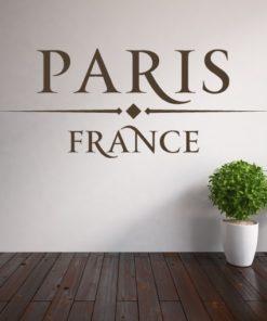 Primer izgleda čokoladno rjave samolepilne stenske nalepke Paris France napis na bež steni v dnevni sobi.