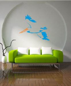 Primer izgleda modre in oranžne samolepilne stenske nalepke Pelican na beli steni v dnevni sobi.