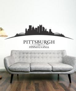 Primer izgleda črne samolepilne stenske nalepke Pittsburgh ukrivljen na beli steni v dnevni sobi. Na nalepki piše: Pittsburgh, Pennsylvania