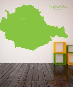 Primer izgleda zelene samolepilne stenske nalepke Podravska na beli steni v dnevni sobi.