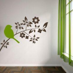 Primer izgleda dvobarvne samolepilne stenske nalepke Ptica na rožasti veji na beli steni v dnevni sobi.